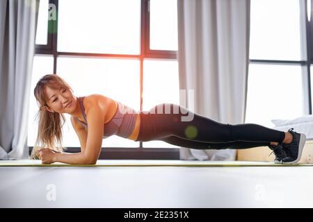 mujer coreana de la aptitud haciendo empuje para arriba, mujer hermosa en el entrenamiento sportswear solamente