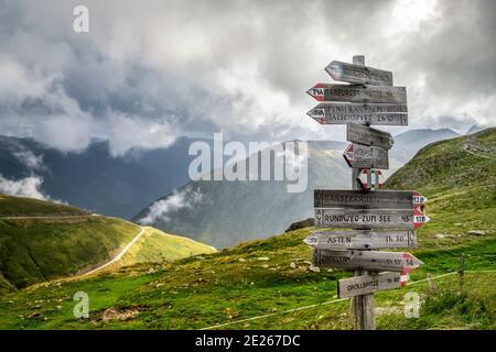 Letrero de madera que muestra las direcciones en un paso de montaña cerca de Penser Joch / Penserjoch en el sur del Tirol, norte de Italia