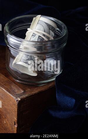Un rollo de 100 billetes en dólares americanos en tarro de vidrio sobre cajón de madera con terciopelo azul sobre fondo negro oscuro, cierre, espacio de copia, financiación an