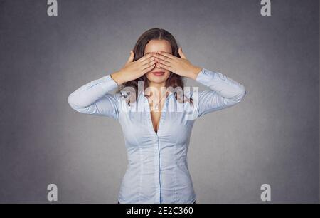 Hermosa mujer joven cubre los ojos con las manos. Primer retrato de una hermosa chica en azul camisa formal aislada sobre fondo gris. Carrera mixta, la suya
