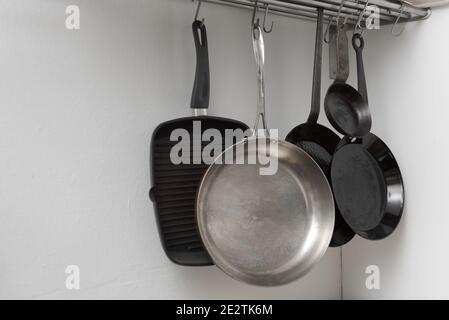 Varias cacerolas en diferentes tamaños y formas para cocinar y. freír colgando en ganchos de metal de la estantería en la cocina con pared blanca de fondo