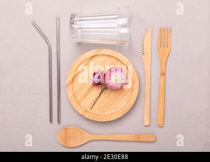 Cero residuos, concepto libre de plástico. Plato de madera, copa de vidrio, juego de cubiertos de bambú. Plano sobre el fondo de lino textil - imagen