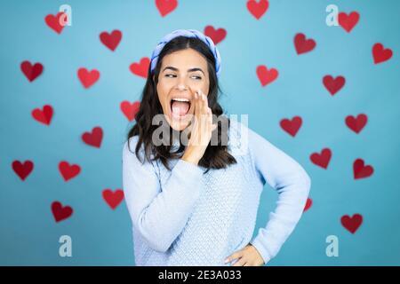 Joven hermosa mujer sobre fondo azul con corazones rojos con la mano en la boca diciendo rumor secreto, susurrando conversación maliciosa de la charla