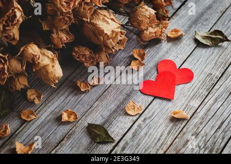 Dos corazones rojos con ramo de rosas secas sobre madera antecedentes