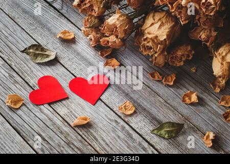 Dos corazones rojos con pétalos de rosas secas sobre madera tabla