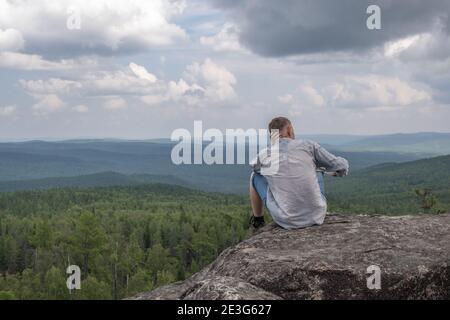 Un hombre libre de mediana edad se sienta en la cima de una montaña, admirando una hermosa vista del valle de la montaña. Unidad con la naturaleza, soledad. Concepto de viaje