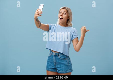 Chica grabando vídeo mostrando seguidores impresionante escena asistiendo a un evento fresco sosteniendo el smartphone con un aspecto impresionado y sorprendido al señalar la pantalla del dispositivo