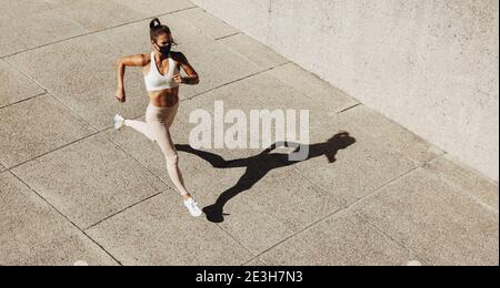 Vista en ángulo alto de una mujer que lleva una máscara facial que se enjuaga al aire libre. Mujer corriendo haciendo ejercicio al aire libre usando una máscara protectora.