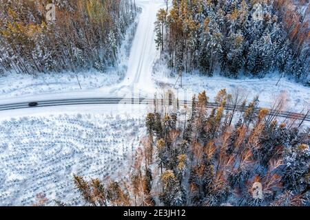 Vista aérea desde el avión del coche sobre la nieve con curvas cubierta camino en el bosque de invierno