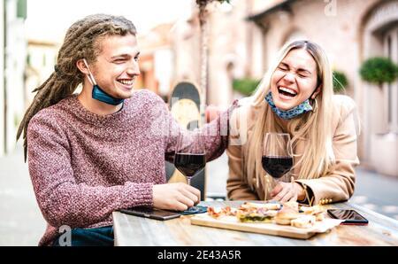 Pareja joven enamorada usando máscara abierta pasándose bien En el bar de vinos afuera - felices amantes de la modernidad pasando el almuerzo juntos en el restaurante dehor