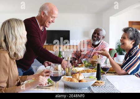 Parejas mayores caucásicas y afroamericanas sentadas en mesa comiendo cena en casa