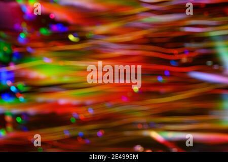 Puntos destocados y líneas horizontales de color rojo, verde, azul y amarillo creados por luces LED fotografiadas al aire libre por la noche.