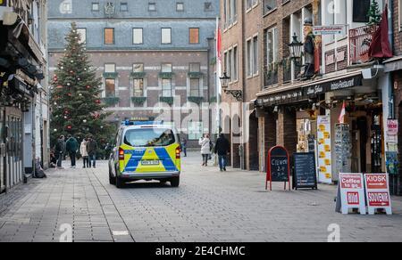 Duesseldorf, Renania del Norte-Westfalia, Alemania - Ciudad vieja vacía de Düsseldorf con árbol de Navidad en tiempos de la crisis de la corona durante la segunda parte del encierro, una patrulla policial verificó las calles vacías de la zona peatonal.