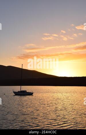La puesta de sol detrás de un velero en el puerto de Molino Viejo, cerca de San Quintín, Baja California, México