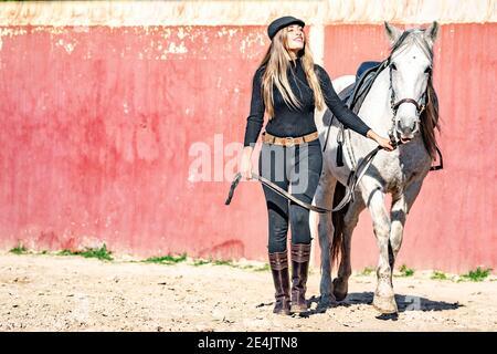 Mujer caminando con caballo en paddock