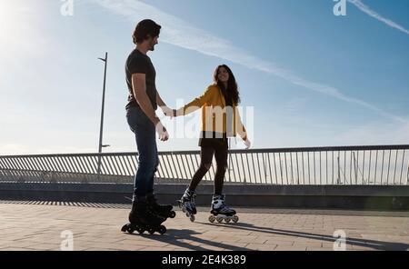Feliz pareja joven sosteniendo las manos mientras patinaba en el muelle