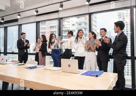 Grupo multiétnico de negocios que se alzaba de manos de éxito después de los negocios seminario en la oficina moderna en el distrito de negocios