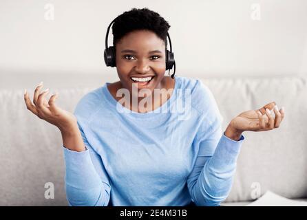 Mujer negra sentada, hablando con la cámara usando el auricular