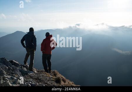 Dos hombres de pie con bastones de trekking en el borde del acantilado y mirando los rayos de la puesta de sol sobre las nubes. Imagen de concepto de cumbre exitosa.
