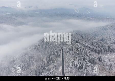 Vista aérea de invierno de la carretera de montaña curva, en Poiana Brasov