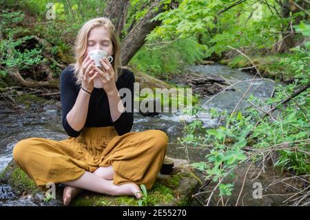 Retrato de una chica joven sentada en cruz con patas en una roca a la orilla de un río, sosteniendo una taza de té china con ambas manos y bebiendo
