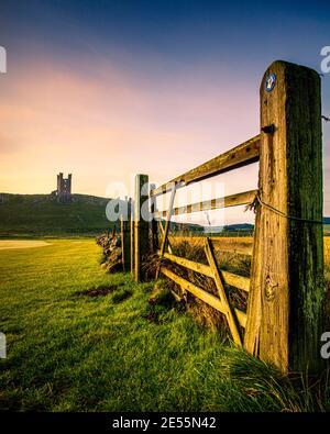 Castillo de Dunstanburgh en Northumberland visto a través de una puerta de campo.