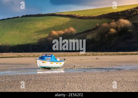 Luz nocturna sobre un barco amarrado en el río Gannel en la marea baja en Newquay en Cornwall.