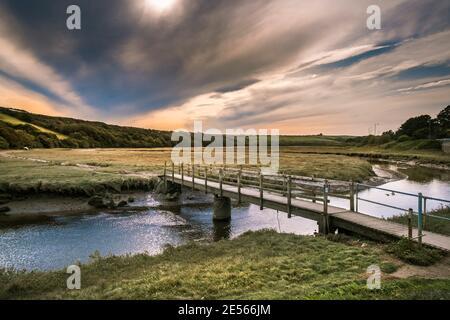 Luz del sol a primera hora de la tarde sobre el río Gannel en la marea baja en Newquay en Cornwall.