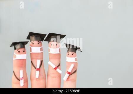 Arte de los dedos de los estudiantes en máscara médica de COVID-2019. Graduados que tienen su diploma después de graduarse.