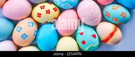Coloridos huevos de caza de Pascua teñidos por el agua coloreada con un hermoso patrón sobre fondo azul pastel, concepto de diseño de vacaciones.
