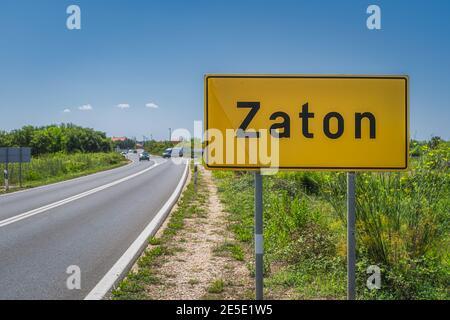 Gran amarillo, ciudad de Zaton signo de bienvenida con coches en una carretera y campo verde en la carretera, Croacia