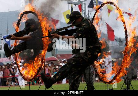 Chinese People's Liberation Army (PLA) soldiers jump through rings of fire in a war game as part of the show for the public during an open day at the Ngong Shuen Chau Naval Base on Hong Kong's Stonecutters Island July 28, 2012. The naval base was open to the public on Saturday, four days ahead of the PLA Army Day on August 1. REUTERS/Tyrone Siu (CHINA - Tags: POLITICS MILITARY)