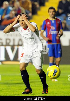 Sevilla's Piotr Trochowsky (L) reacts as Levante's Xavi Venta looks on during their Spanish first division soccer match at the Ciudad de Valencia Stadium in Valencia December 10, 2011. REUTERS/Heino Kalis (SPAIN - Tags: SPORT SOCCER)