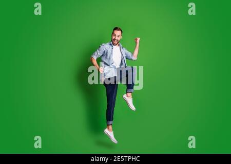 Foto de perfil de tamaño completo de divertido hombre impresionado salto de desgaste azul camisa pantalones vaqueros calzado aislado sobre fondo de color verde