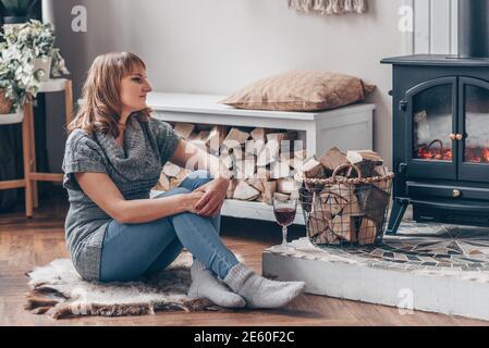 Mujer joven y sonriente se sienta cerca de la fogata en otoño o, casa en el bosque. Concepto de relajación invernal.