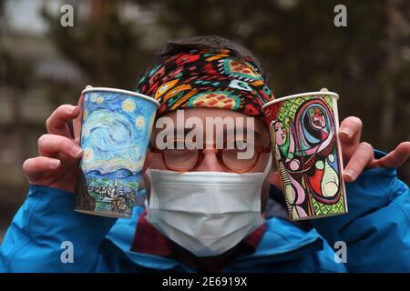 Pekín, Turquía. 27 de enero de 2021. Berk Armagan, un joven de 26 años de Estambul, muestra sus pinturas en vasos de papel en Ankara, Turquía, 27 de enero de 2021. Un artista turco autodidacta y viajero dibuja los sitios en todo el mundo que visita en simples tazas de café de papel que utiliza como lienzo para financiar su pasion lúgubre. Crédito: Mustafa Kaya/Xinhua/Alamy Live News