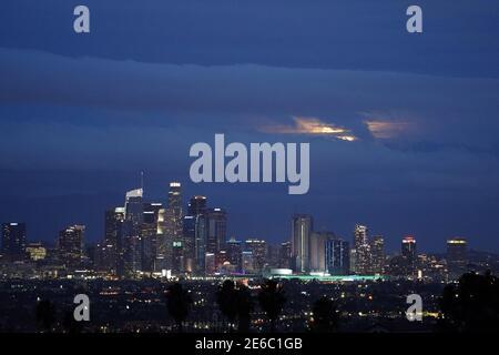 Los Angeles, Estados Unidos. 28 de enero de 2021. Una luna llena se eleva a través de nubes de tormenta sobre el horizonte del centro de los Ángeles el jueves, 28 de enero de 2020. Photo via Credit: Newscom/Alamy Live News