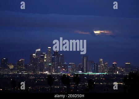 Una luna llena se eleva a través de nubes de tormenta sobre el horizonte del centro de los Ángeles el jueves, 28 de enero de 2020.