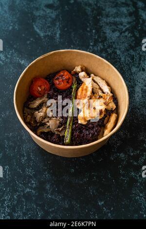 Cuenco de comida saludable con pollo, arroz negro o arroz salvaje, champiñones, puré de aguacate y tomates asados a la parrilla en cuenco de plástico para llevar listo para comer. Foto de stock