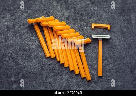 Muchas de plástico desechable barato afeitado de color naranja amarillo con las almohadillas de fondo gris, juego de herramientas de eliminación del cabello