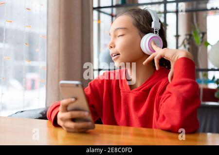 Niña adolescente escuchando la música a través de auriculares y cantando - aplicación en línea en el teléfono móvil. Concepto de tecnología moderna.