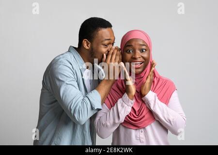 Hombre negro compartiendo rumor con su novia emocionada