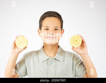 Retrato de un joven caucásico encantador muestra dos rodajas de limón.Boy mirar a una cámara.