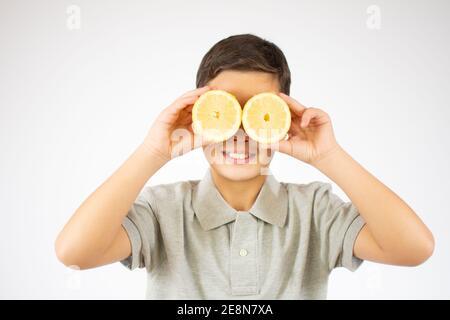 Feliz niño de jengibre que cubre sus ojos con limones y sonrisa en una pared blanca del estudio