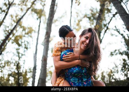 Mujer piggybacking feliz novia mientras disfruta en el bosque