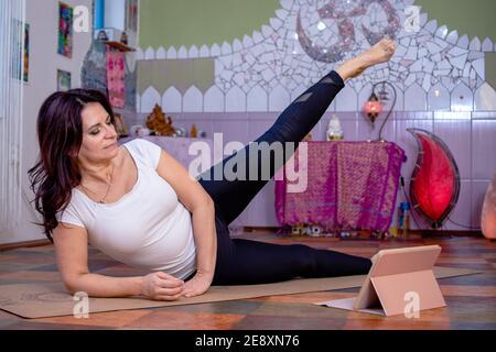 Hermosa mujer mayor activa haciendo ejercicio o dando clases en línea en casa en la computadora portátil durante la cuarentena. Retrato completo. Yoga, pilates.