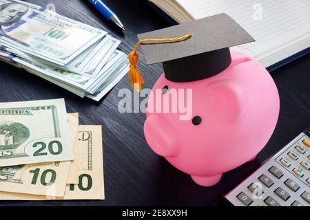 Ahorros para el concepto de educación y universidad. Banco de piggy rosa con tapa de graduación y dinero.