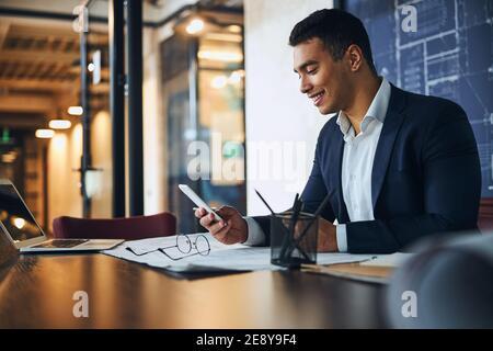 Ingeniero leyendo un mensaje de texto en su oficina