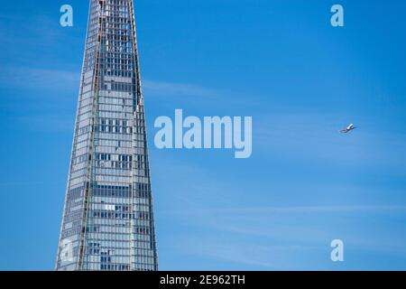 Baja volando avión de pasajeros cerca de la Shard en su aproximación final para aterrizar en el aeropuerto de la City de Londres, Inglaterra, Reino Unido.