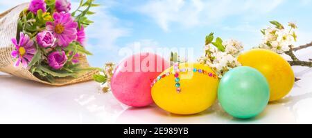 Huevos de Pascua de colores sobre el cielo azul nublado con ramo de flores, primer plano, banner de vacaciones